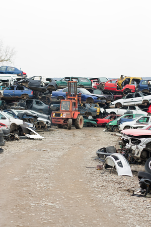 piled: Piled up destroyed cars in the junkyard.