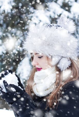 snowball: Beautiful young woman enjoying making a snowball. Stock Photo