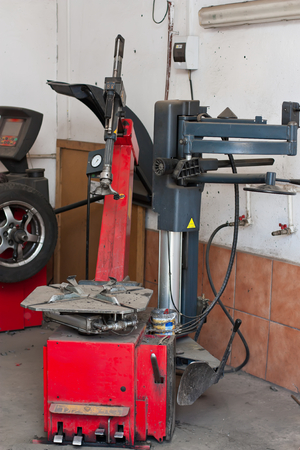 wheel balancing: A tire changer device in an automobile repair shop, with a wheel balancing machine in the background.