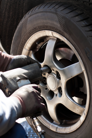pneumatic tyres: Removing the wheel of a car in the automobile repair shop. Stock Photo