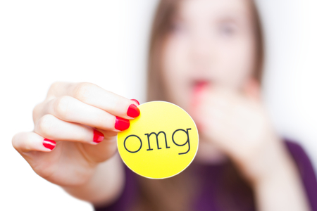 reacting: Close-up of girl reacting surprised holding up an omg sign isolated on white with faded background.