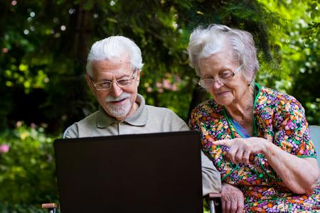 usando computadora: Una pareja de ancianos se divierten con el portátil en el jardín, al aire libre.