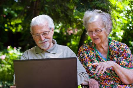 couple having fun: An elderly couple having fun with the laptop in the garden, outside. Stock Photo
