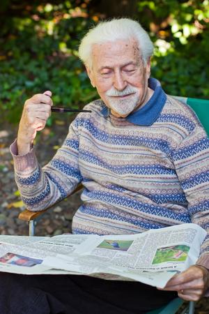 Elderly gentleman reading the newspaper outside in the garden.