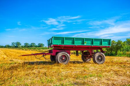 Old green trailer on the field. Harvest time. poland