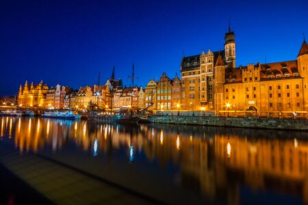 View of the old city - Historic port crane over Motlawa river in Gdansk at night, Poland Stock Photo