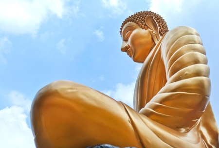 Thai Buddha Golden Statue against blue sky photo