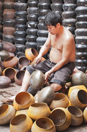 BANGKOK, THAILAND - September 26:  An unidentified man make Bat (The alms bowl used by monks to receive donations of foods in the morning)  on September  26, 2011 at Ban Bat Community, Bangkok,Thailand.