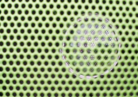 Green speaker grille close-up  Use for texture or background  Shallow depth of field photo