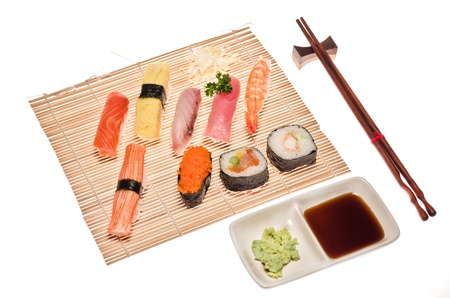 Assorted japanese sushi on bamboo mat isolated in white background photo