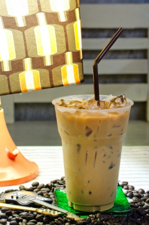 Delicious cold coffee drink with ice on table photo