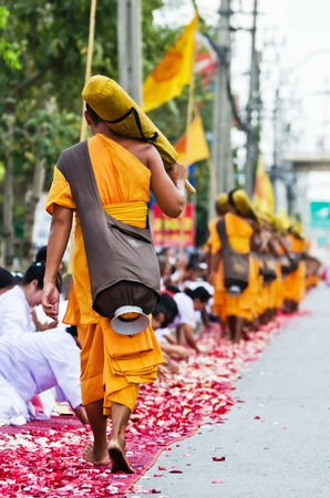 BANGKOK  THAILAND-January 21: Row of Buddhist hike monks on streets strewn with rose petals on the Thammachai hike establish the path of the great teachers, Bangkok, Thailand. January 21, 2012