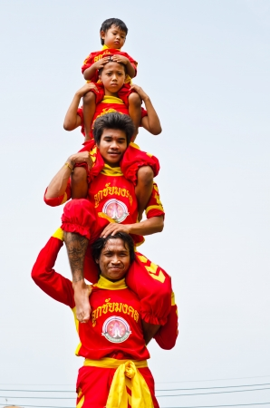 NAKHON PATHOM, THAILAND -OCTOBER  15: Group of men and boys are doing pyramid acrobats  at  The Nine Emperor Gods Festival on October 15, 2012 in Nakhon Pathom, THAILAND. Editorial