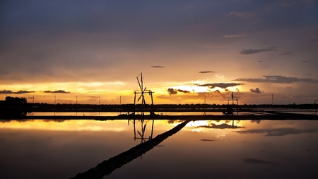 Beautiful sunset view of salt farm and wind wheel in Thailand photo
