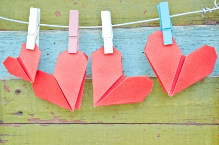 paper heart hanging on the clothesline. On old wood background. Valentines day theme . Standard-Bild