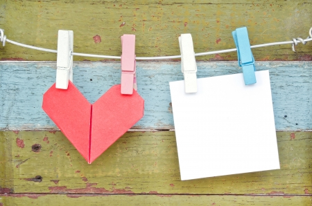Paper heart and card hanging on the clothesline. On old wood background.Valentines day theme . photo