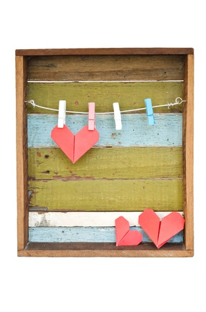 Paper heart hanging on the clothesline. On old wood background.Valentines day theme .