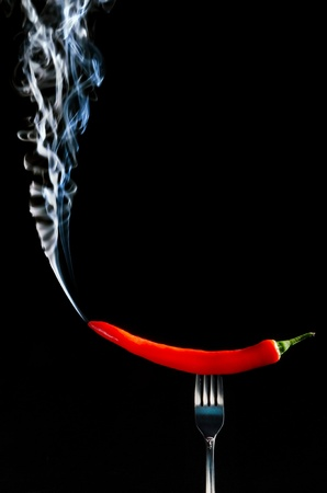 Red hot chilli pepper on fork with smoke against  black background  photo