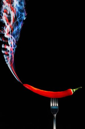 Red hot chilli pepper on fork with smoke against  black background  Stock Photo