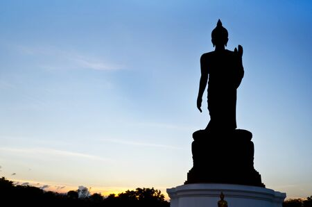 silhouette of walking Buddha against  blue sky in  Buddhist park at Phutthamonthon district, Nakhon Pathom , Thailand