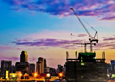 Industrial construction cranes and city  at sunrise  Stock Photo