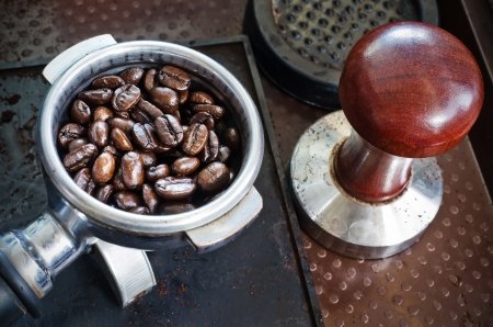 tamper: Espresso filter filled with fresh roasted coffee beans and tamper in coffee shop