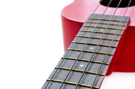 Part of red ukulele isolated on white background. Soft focus.