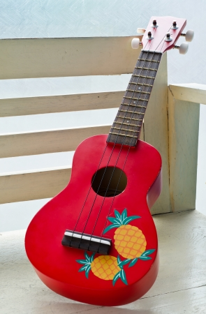 Red Ukulele guitar on wooden chair Stock Photo - 20361916