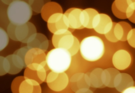 Defocused abstract gold bokeh against a dark background for use at graphic design Stock Photo