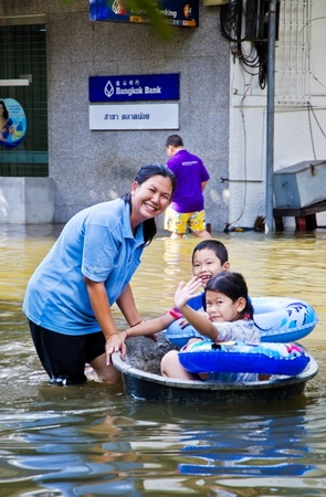 BANGKOK, THAILAND - OCT 29: Unidentified people use black basin as a boat to transport  during the worst flooding on October 29, 2011 in Bangkok, Thailand Stock Photo - 20648567