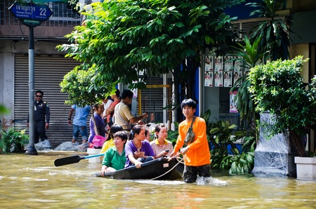 worst: BANGKOK, THAILAND - OCT 31:  An unidentified volunteer use a boat to transport flood victims during the worst flooding on October 31, 2011 in Bangkok, Thailand