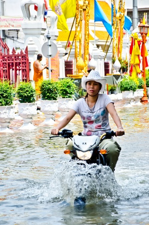 rains: BANGKOK, THAILAND - OCT 30: An unidentified motorbike rider navigates a flooded street after the heaviest monsoon rains in over 50 years on October 30, 2011 in Bangkok, Thailand