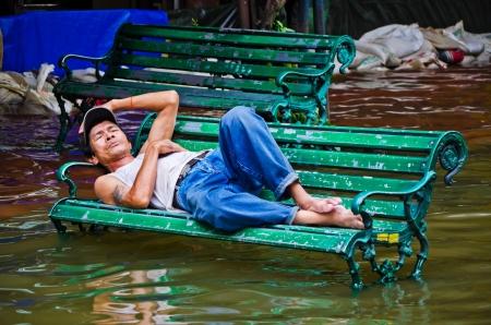 BANGKOK, THAILAND - OCT 31: Flood victim becomes homeless, sleep on bench at Bangkok