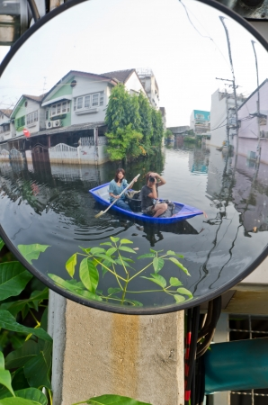 BANGKOK, THAILAND - NOV 5: Scene from defensive driving mirror with  flooded house  reflected on it during the worst flooding on November 5, 2011 in Bangkok, Thailand