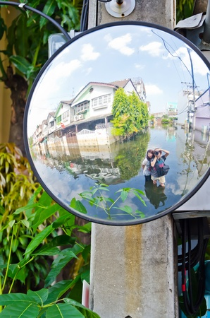 BANGKOK, THAILAND - NOV 11: Scene from defensive driving mirror with  flooded house  reflected on it during the worst flooding on November 11, 2011 in Bangkok, Thailand Editorial