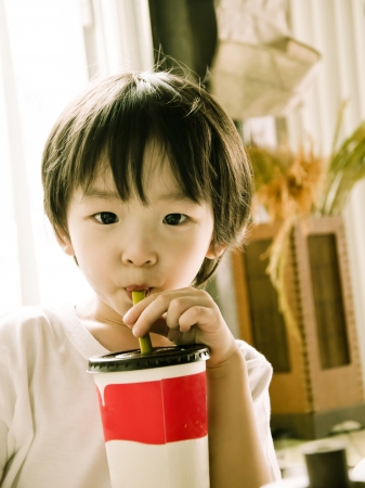 portrait of cute asian boy drinking ice green tea Stock Photo