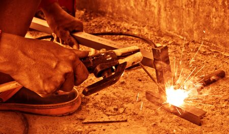 Closeup view of worker welding  two pieces of metal together,vintage  color tone