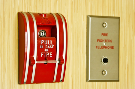 Red Fire alarm and fire fighter telephone on the wooden wall photo