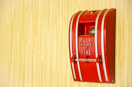 Red Fire alarm on the wooden wall with text area. photo