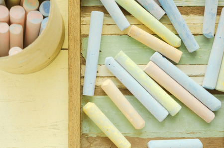 Close-up of colorful chalks on wooden table, soft tone processed. Stock Photo