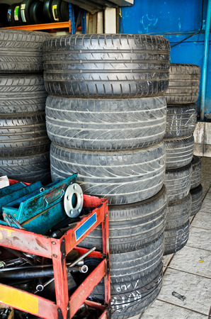Stack of used car tires waiting to be recycled in garage  photo