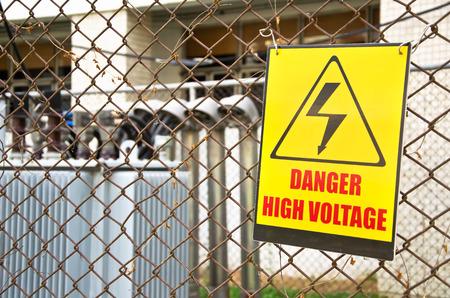 Danger high voltage warning sign on a fence in transformer station