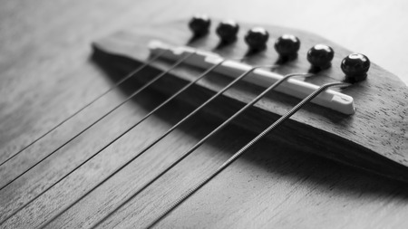 detail of acoustic guitar focus on  strings, very shallow depth of field. Black & White.