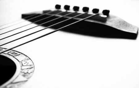 detail of acoustic guitar focus on bridge and strings, very shallow depth of field. Black & White