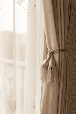 Curtain with curtain tieback at window, selective focus.  Processed with vintage style. Stock Photo