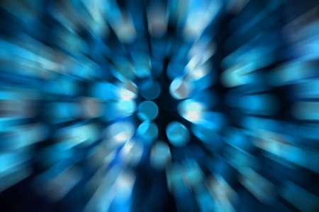 Abstract blue circular bokeh against dark background with zoom effect for use at graphic design