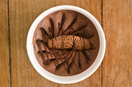 Overhead view of  homemade Chocolate Italian ice cream tub on wooden background , very shallow depth of field.