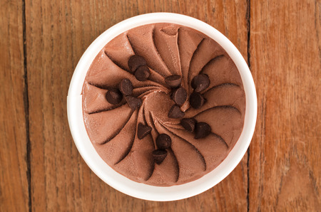 Overhead view of  homemade Chocolate chip Italian ice cream tub on wooden background