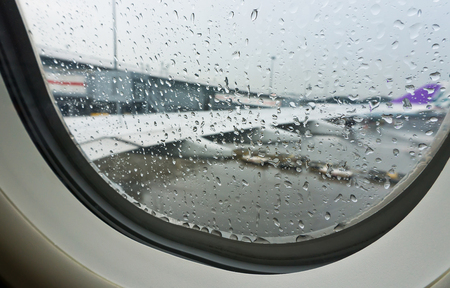 drop off: selective focus rain drop from window seat inside airplane with blurred wing background at  plane park in airport before taking off