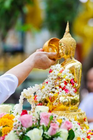 thai buddha: people showering buddha statue on Songkran festival in Thailand, very shallow depth of field.